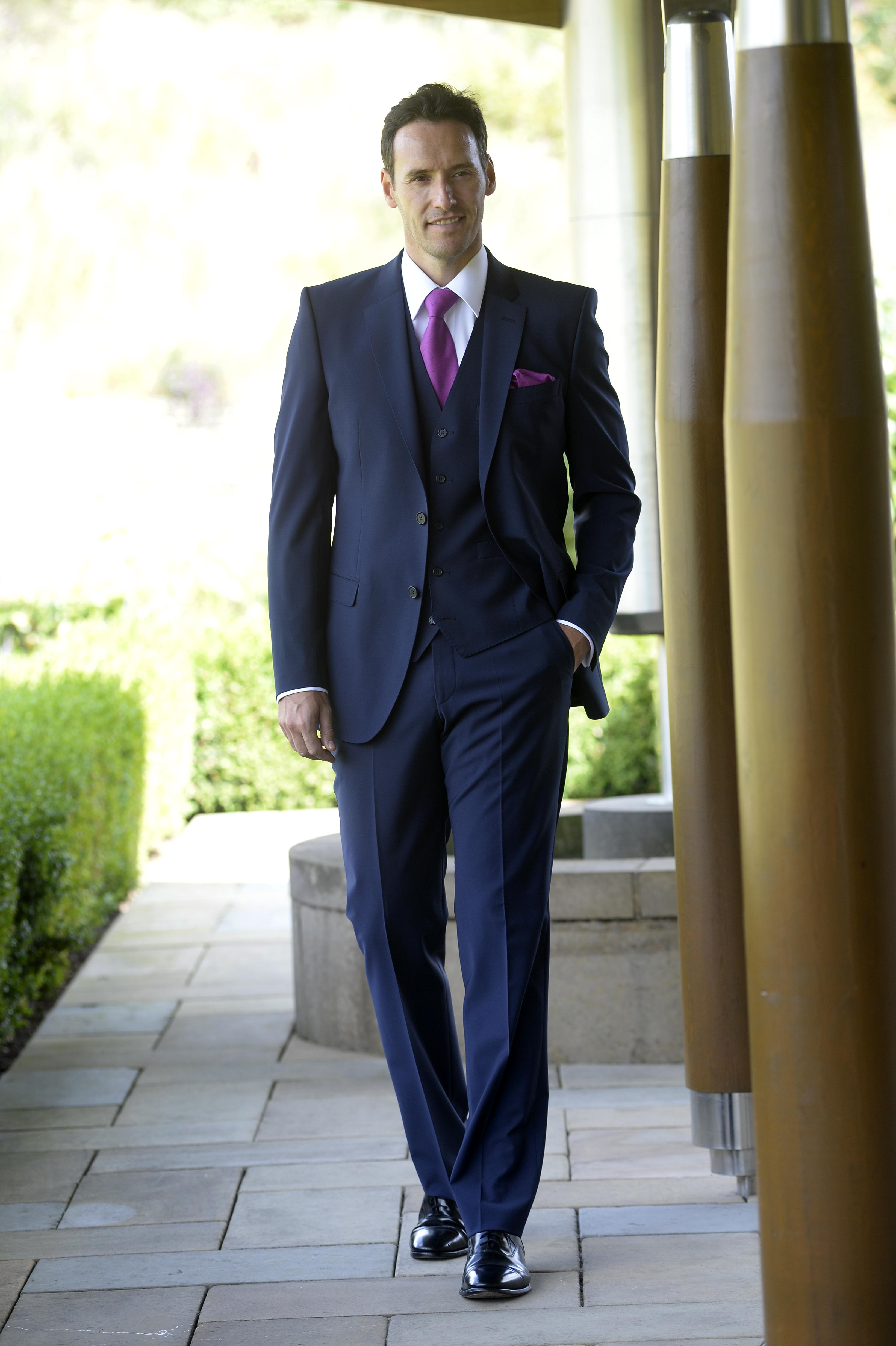 Blue slim fit suit with matching waistcoat and magenta tie and handkerchief